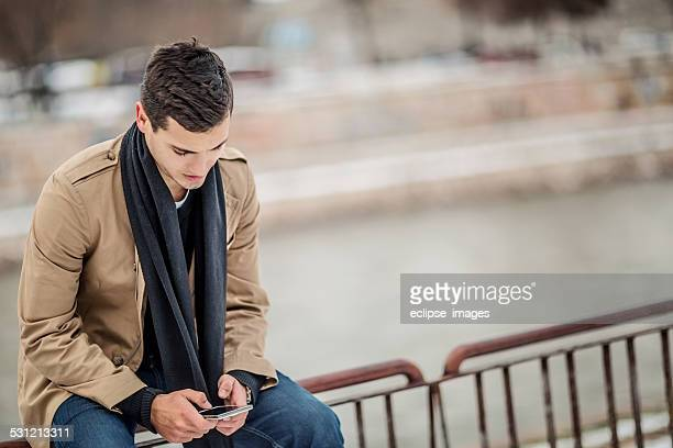 young man using a smart phone - only young men stock pictures, royalty-free photos & images