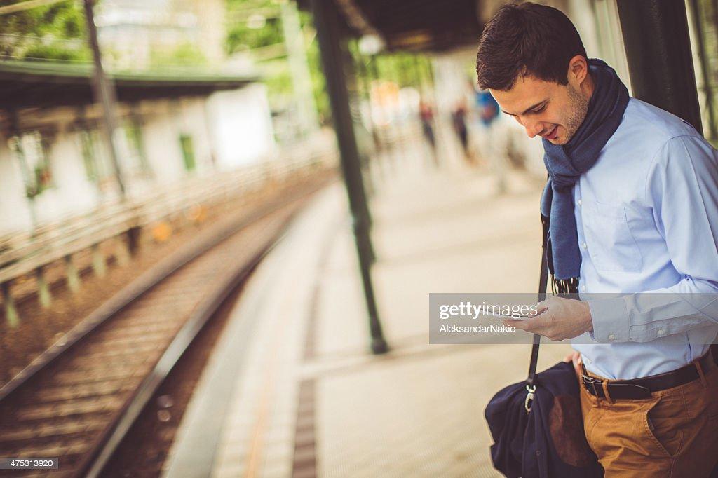 、スマートフォンを使用して若い男の鉄道駅 : ストックフォト