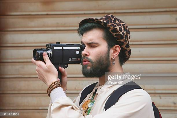 young man using a vintage video camera - industrial door stock pictures, royalty-free photos & images