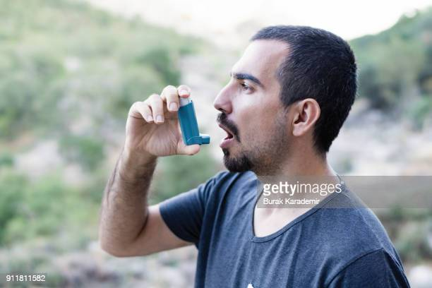 young man using an asthma inhaler - asthmatic stock photos and pictures