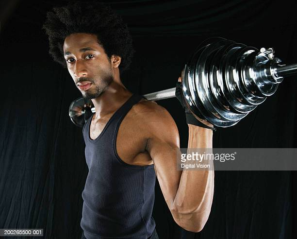 Young man using barbell, portrait