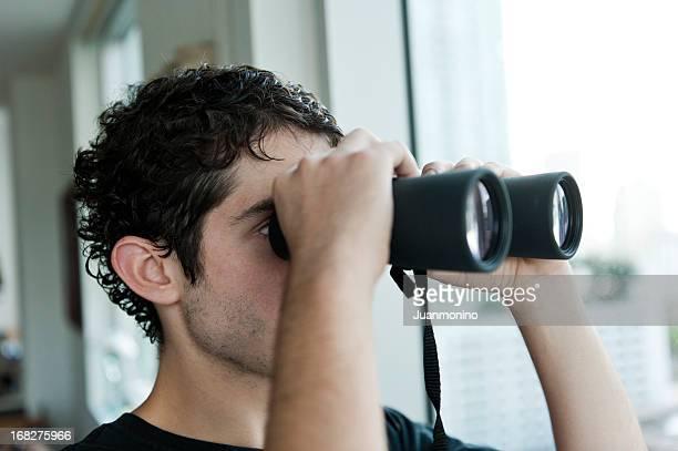 joven con binoculares - voyeurismo fotografías e imágenes de stock