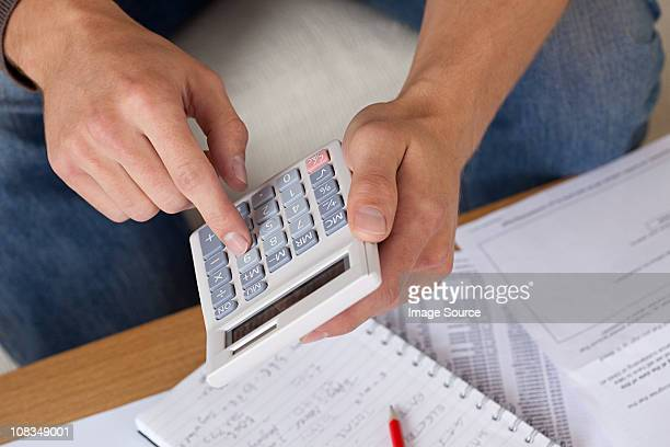 Young man using calculator