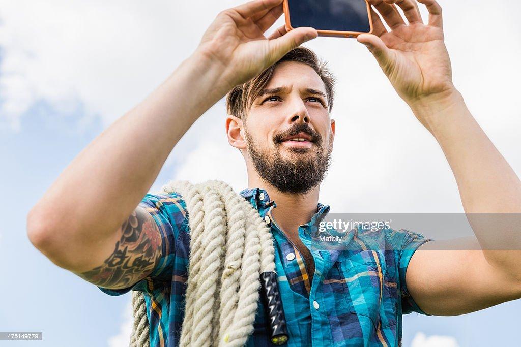 Young man using camera phone : Stock Photo