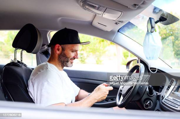 young man using cell phone in car at afternoon. - stock photo. - travelstock44 stock pictures, royalty-free photos & images
