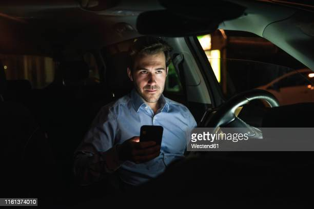 young man using cell phone in car at night - one man only stock pictures, royalty-free photos & images