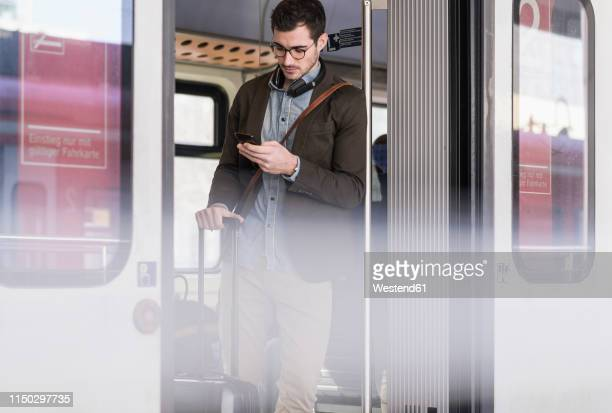 young man using cell phone in commuter train - passenger train stock pictures, royalty-free photos & images
