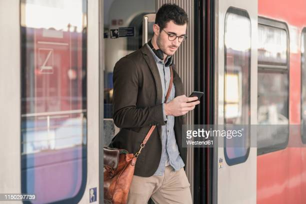 young man using cell phone in commuter train - crossbody bag stock pictures, royalty-free photos & images