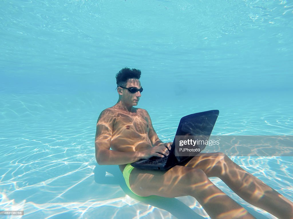 Young man using computer underwater : Stock Photo