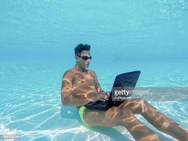 Young man using computer underwater