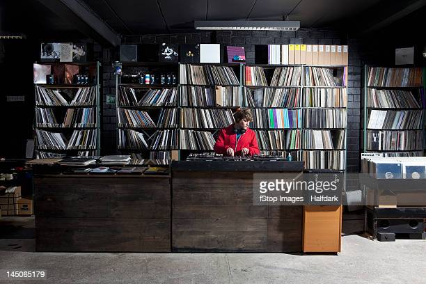 a young man using decks and a sound mixer at a record store - group f stockfoto's en -beelden