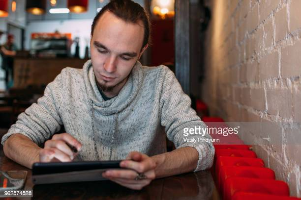 Young man using digital tablet at cafe