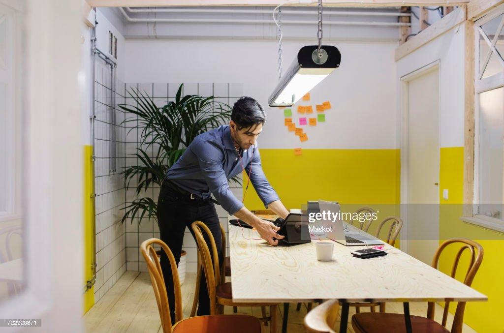 Young Man Using Digital Tablet At Desk