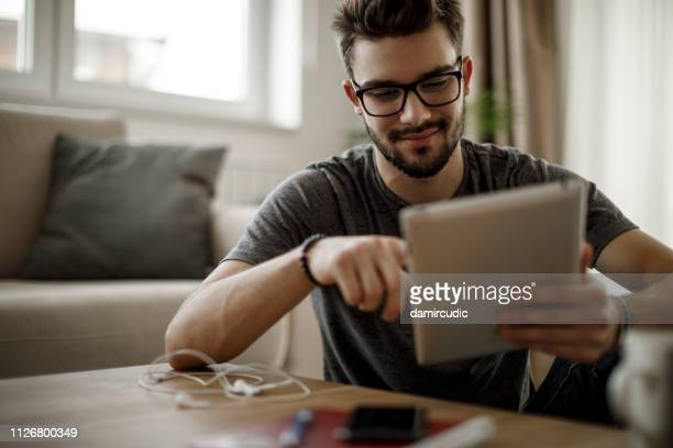 young man using digital tablet at home - using digital tablet stock pictures, royalty-free photos & images
