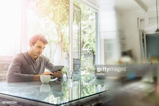 Jeune homme à l'aide de tablette numérique de table