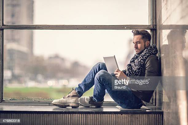 Joven usando tableta digital junto a la ventana.