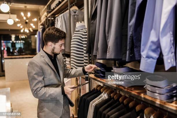 giovane che utilizza tablet digitale per l'inventario - abbigliamento da uomo foto e immagini stock