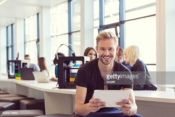 Young man using digital tablet in 3D printer office