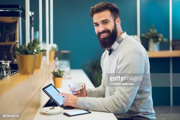 Hombre joven con tableta digital en barra de café