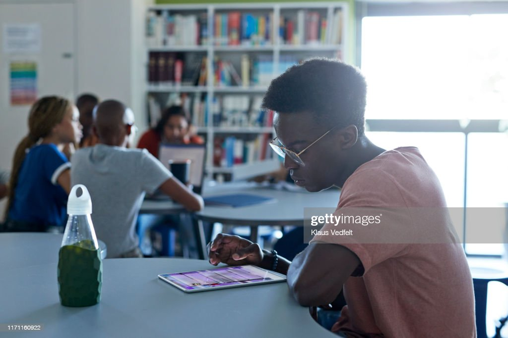 Young man using digital tablet in library : Stock Photo