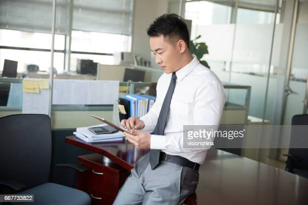 young man using digital tablet in office