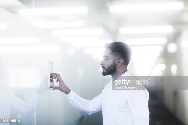 young man using digital tablet in office - sigrid gombert stock pictures, royalty-free photos & images