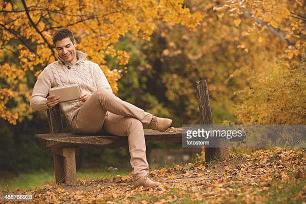 Junger Mann mit digitalen tablet auf park bench