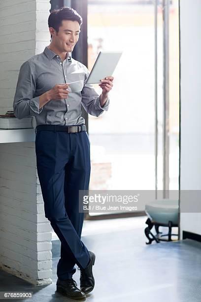young man using digital tablet - オープンネック ストックフォトと画像