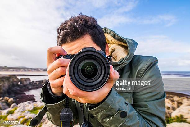 young man using dslr camera - photographer stock photos and pictures
