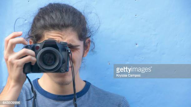 Young man using DSLR camera