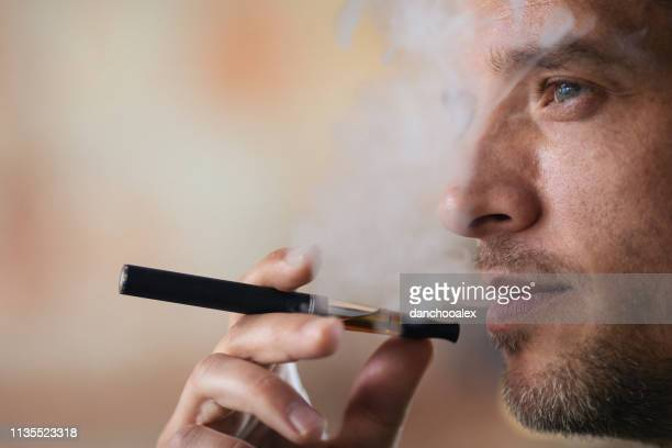 junger mann mit elektronischer zigarette - gift hand stock-fotos und bilder