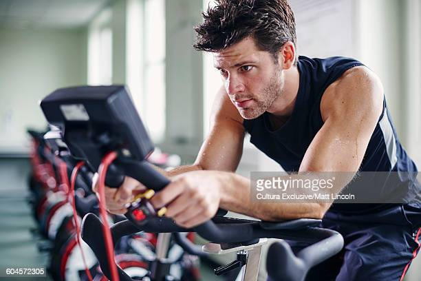 Young man using exercise bike