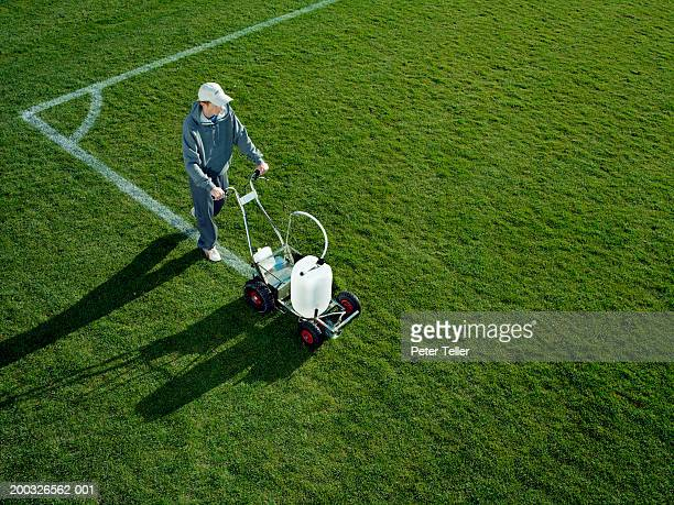 young man using field line marker, elevated view - sports equipment stock pictures, royalty-free photos & images