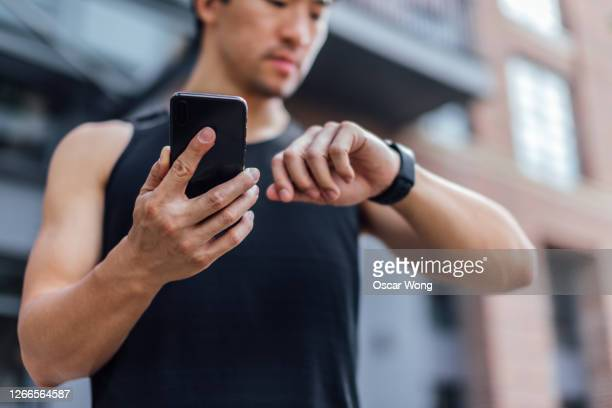 young man using fitness app on smart phone and smart watch for tracking workout - smart watch stock pictures, royalty-free photos & images