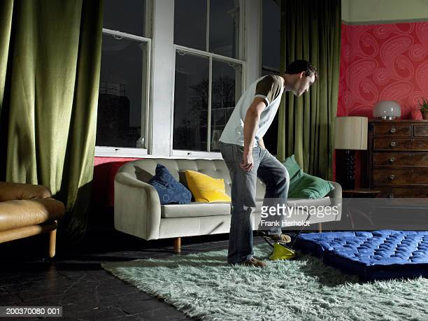 Young man using foot pump on air mattress in living room