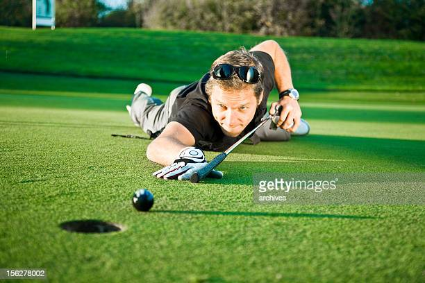 Junger Mann mit Golf Club und Billard Queue on Green