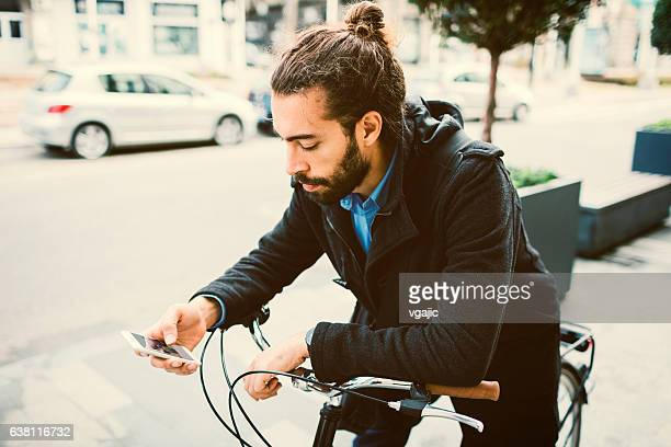 Young Man Using His Smart Phone On Bicycle.