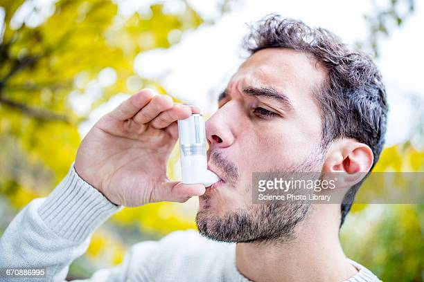 Young man using inhaler