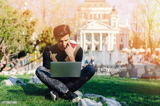 Young man using lap top outside