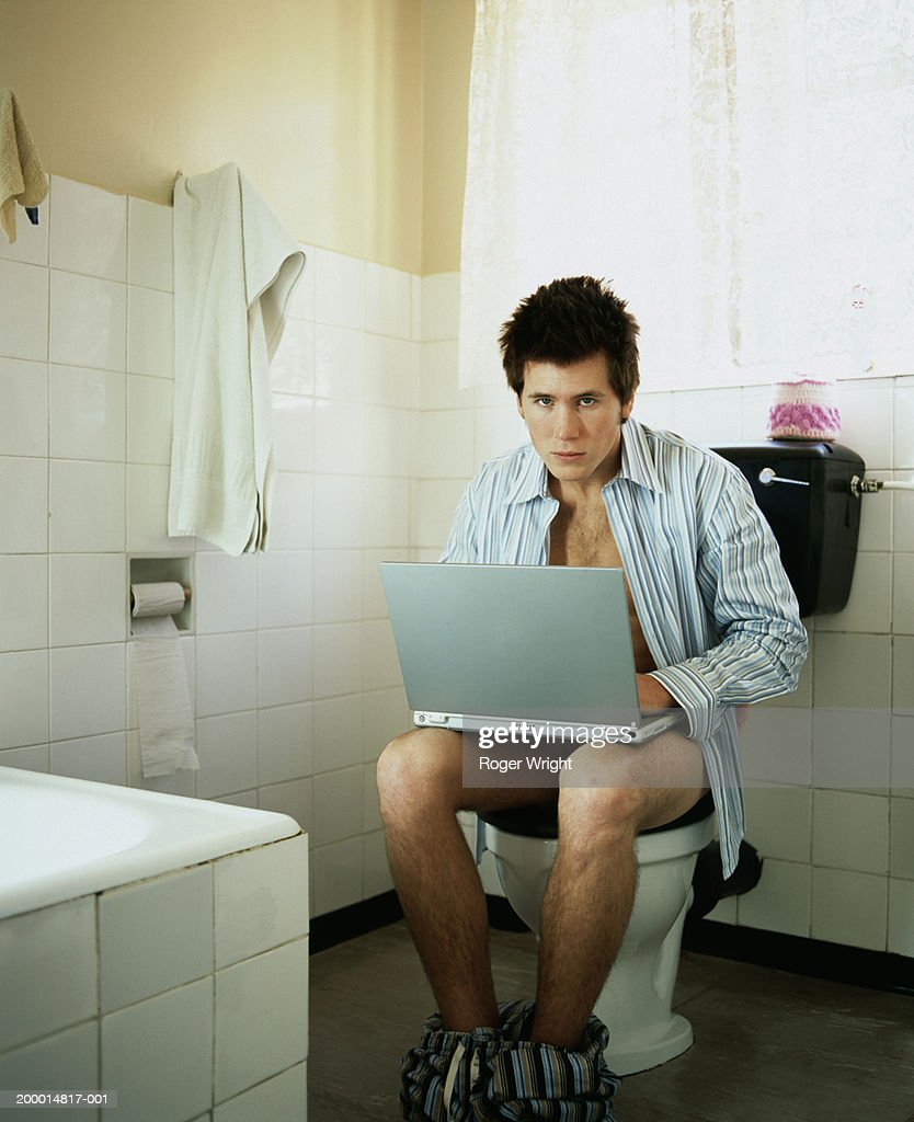 young boy and the toilets Young man using lap top whilst on toilet, portrait : ストックフォト