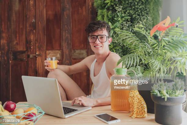 young man using laptop and drinking orange juice at home - nerd stock pictures, royalty-free photos & images
