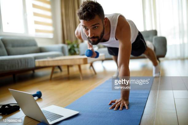 young man using laptop and exercising at home - muscular build stock pictures, royalty-free photos & images