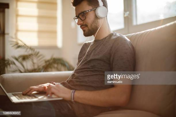 young man using laptop and listening to music at home - stream stock pictures, royalty-free photos & images