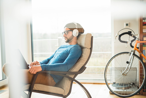 Young man using laptop and wearing headphones - gettyimageskorea