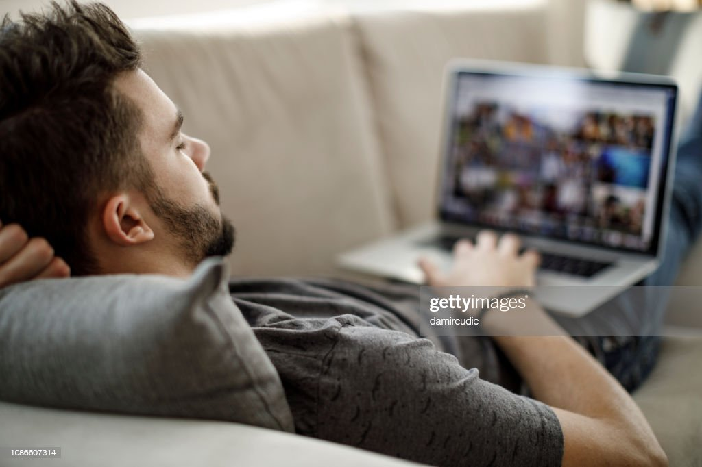 Young man using laptop at home : Stock Photo