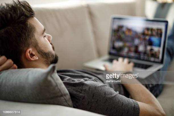 young man using laptop at home - stream stock pictures, royalty-free photos & images
