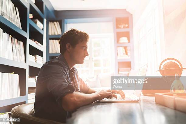 young man using laptop at table - authors stock photos and pictures