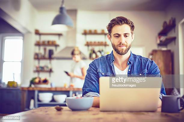 Young man using laptop at table with woman in background