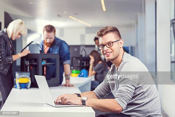 Young man using laptop in 3D printer office