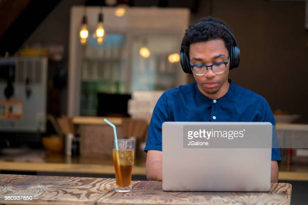 Young man using laptop in a cafe